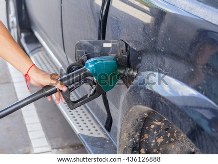 transportation and ownership concept -man pumping diesel fuel .
