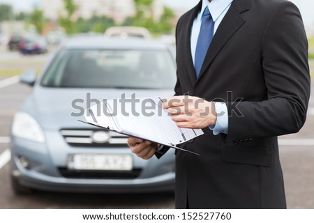 transportation and ownership concept - man with car documents outside - stock photo