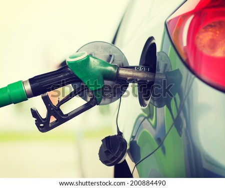 transportation and ownership concept - pumping gasoline fuel in car at gas station - stock photo