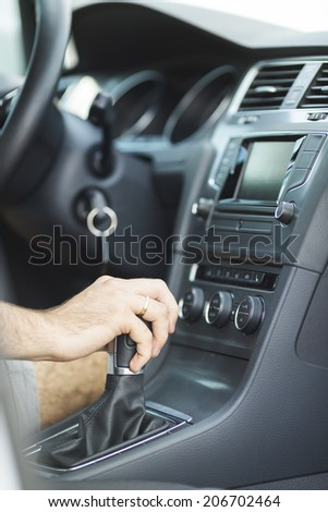 transportation and vehicle concept - man shifting the gear on car manual gearbox - stock photo