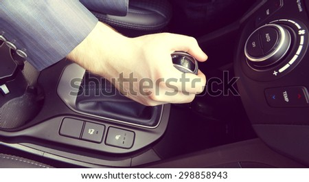 transportation and vehicle concept - man shifting the gear on car manual gearbox.Parking gear..Hand of the driver of the car , toned.