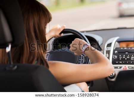 transportation and vehicle concept - woman driving a car and looking at watch