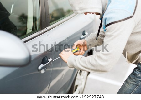 transportation, crime and ownership concept - thief breaking the car lock - stock photo