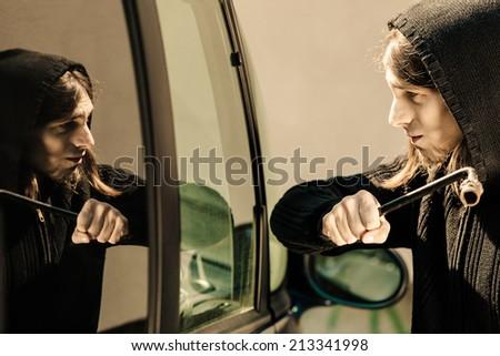 Transportation, crime and ownership concept - thief burglar breaking smashing the car window - stock photo