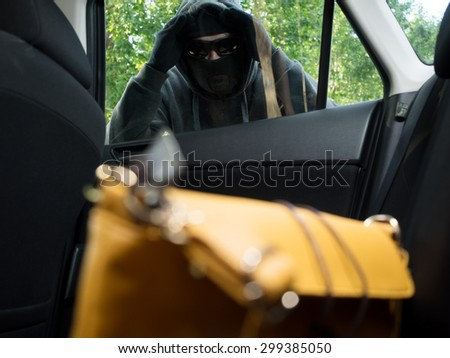 Transportation crime concept .Thief stealing bag from the car - stock photo
