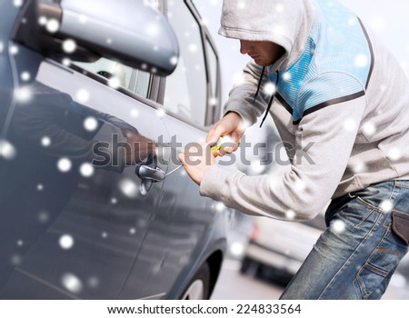 transportation, crime, people and burglary concept - thief breaking car lock screwdriver - stock photo