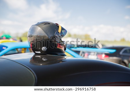 transportation, high speeds, racing and road concept - close up of car on autodrome or parking with helmet on roof top from back - stock photo
