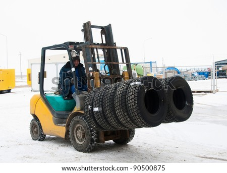 Transportation of autotyres by a loader - stock photo