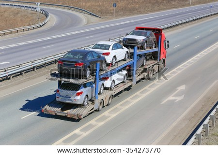 transportation of car on semi-trailer on country highway - stock photo