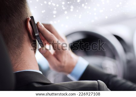 transportation, people, technology and vehicle concept - close up of man using smartphone while driving car - stock photo