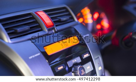 Transportation vehicle and car auto audio concept - Car audio and radio stereo system on car panel in evening light