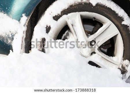 transportation, winter and vehicle concept - closeup of car wheel stuck in snow - stock photo