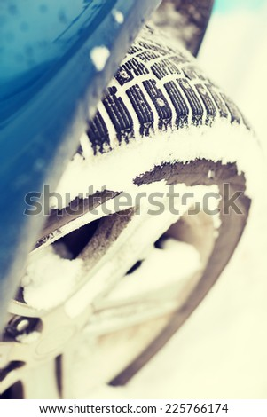transportation, winter and vehicle concept - closeup of car winter tire - stock photo