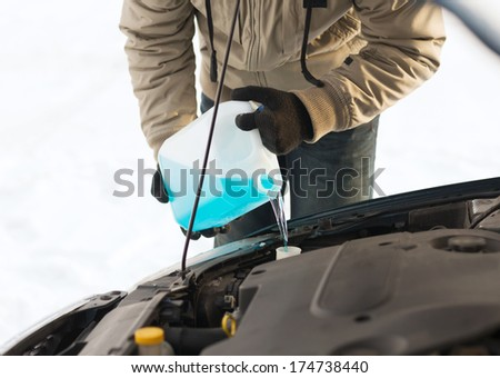 transportation, winter and vehicle concept - closeup of man pouring antifreeze into windscreen water tank - stock photo