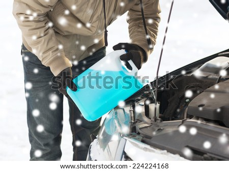 transportation, winter, people and vehicle concept - closeup of man pouring antifreeze into car - stock photo