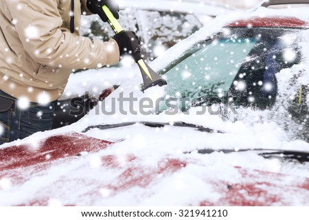 transportation, winter, weather, people and vehicle concept - closeup of man cleaning snow from car windshield with brush - stock photo