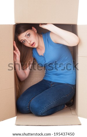 Trapped inside. Shocked young woman looking at camera while sitting in a cardboard box - stock photo