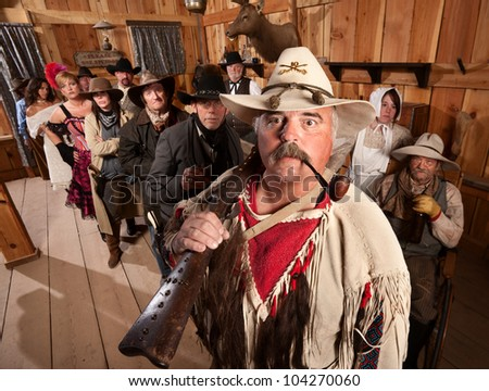 Trapper with rifle over his shoulder in an old western tavern - stock photo