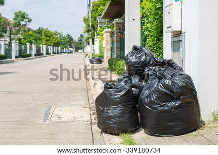 Trash bag ,black plastic garbage bags front of house. - stock photo