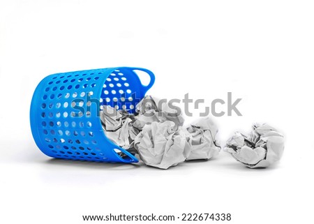 Trash basket filled with crumbled paper canted on a side isolated on white background  - stock photo