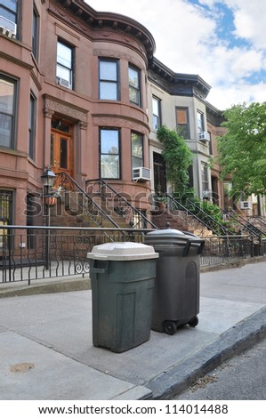 Trash Can Containers on sidewalk of urban brownstone residential neighborhood - stock photo