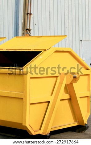 Trash can dustbins big yellow outside - stock photo