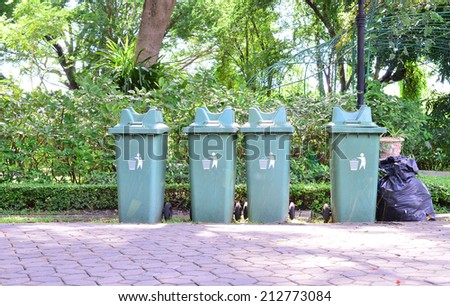 trash cans (garbage bin) in the park beside the walk way - stock photo