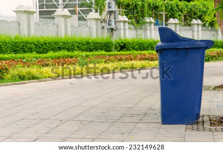 trash cans in the park beside the walk way. - stock photo