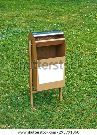 Trash container for smokers on the lawn in the park - stock photo
