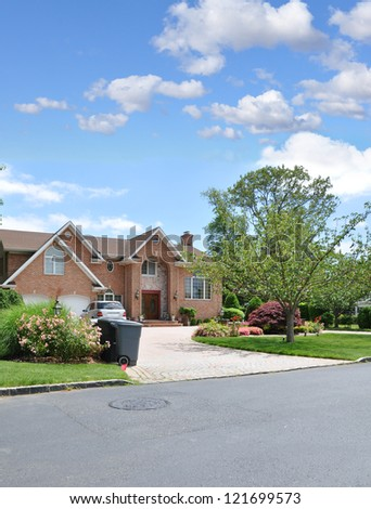 Trash Day Suburban Neighborhood Large Brick McMansion Style Architecture Home Sunny Blue Sky Day Clouds