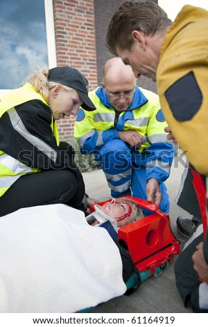 Trauma team providing medical attention to a wounded woman on a stretcher wearing a neck brace - stock photo