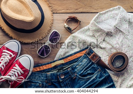 Travel accessories and costume on wooden floor - stock photo