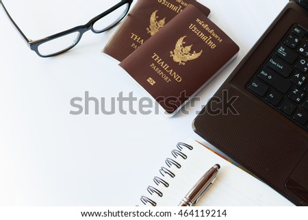 Travel accessories costumes. Passports Thailand, Preparation for travel, Notebook pen on top, glasses, and laptop or computer for vacation time, soft focus.