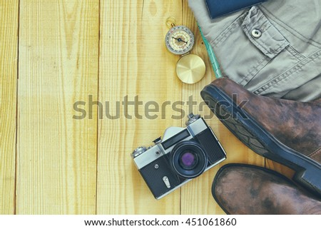 travel accessories over wooden background, old camera, man shoes and compass. retro style image