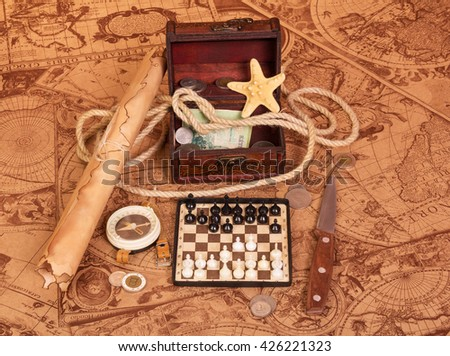 Travel Accessories: scroll, compass, chess, treasure chest, money, coins, a knife and a rope on the background of antique maps.