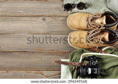 Travel accessories set on wooden background: old hiking leather boots, pants, backpack, map, vintage film camera and sunglasses. Top view point. - stock photo