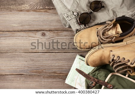 Travel accessories set on wooden background: old hiking leather boots, pants, backpack, map and sunglasses. Top view point.