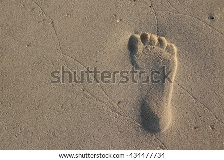 travel, adventure and beach concept - footprint on sand - stock photo