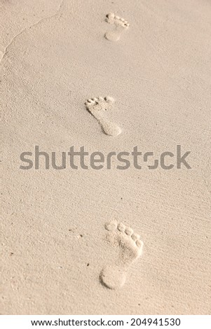 travel, adventure and beach concept - footprints on sand