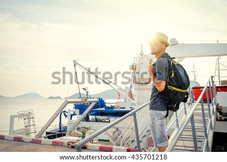 Travel and adventures. Young man with rucksuck on the ship stairs bridge. - stock photo