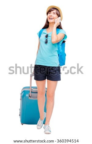 Travel and technology. Full length studio portrait of pretty young woman with luggage talking on smartphone. Isolated on white. - stock photo