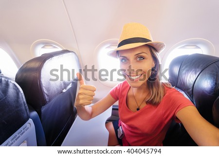 Travel and technology. Young woman in plane taking selfie while sitting in airplane seat. - stock photo