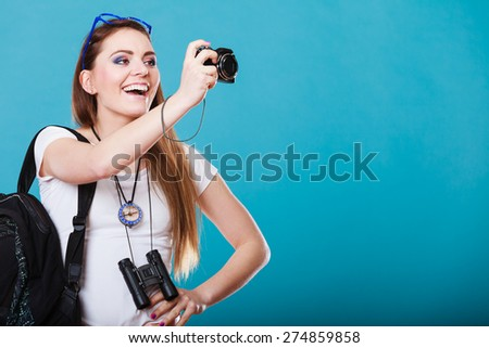 Travel and tourism active lifestyle concept. Tourist woman with backpack taking photo with camera on blue