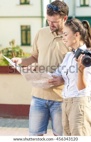 Travel and Vacations Concepts. Happy Young Couple Traveling Together. Exploring City Map in City. Vertical Image Orientation - stock photo