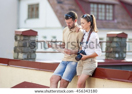 Travel and Vacations Concepts. Happy Young Couple Traveling Together. Exploring City Map in City. Horizontal Image Orientation - stock photo