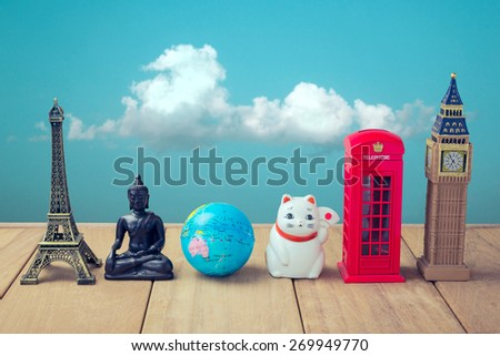 Travel around the world concept. Souvenirs from around the world on wooden table over blue sky background - stock photo