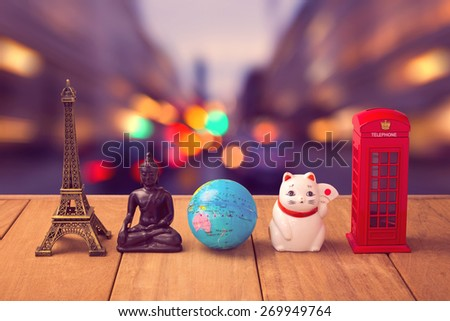 Travel around the world concept. Souvenirs from around the world on wooden table over city bokeh background - stock photo