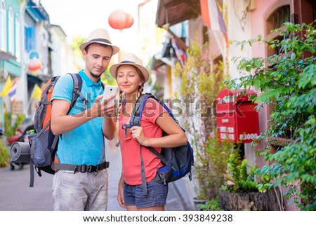 Travel Asia. Young couple looking at phone travelling Asia. - stock photo