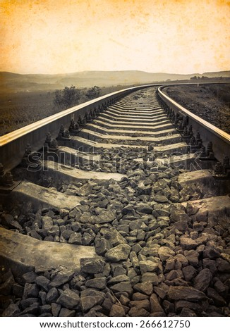 Travel background at old paper texture with empty copy-space for your text. Monochrome railway. Railroad tracks in retro style for travel concept. Old rail road on vintage photo, sepia colors. - stock photo