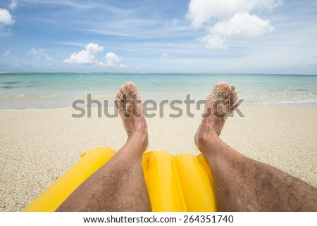 travel background with a man´s legs on a yellow air mattress at a beautiful beach with a turquoise sea